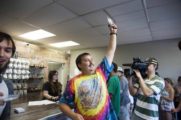 Mike Boyer showing off his purchase as the first in line to legally purchase marijuana at Spokane Green Leaf, Tuesday, July 8, 2014, in Spokane, Wash. (AP Photo/The Spokesman-Review, Dan Pelle)