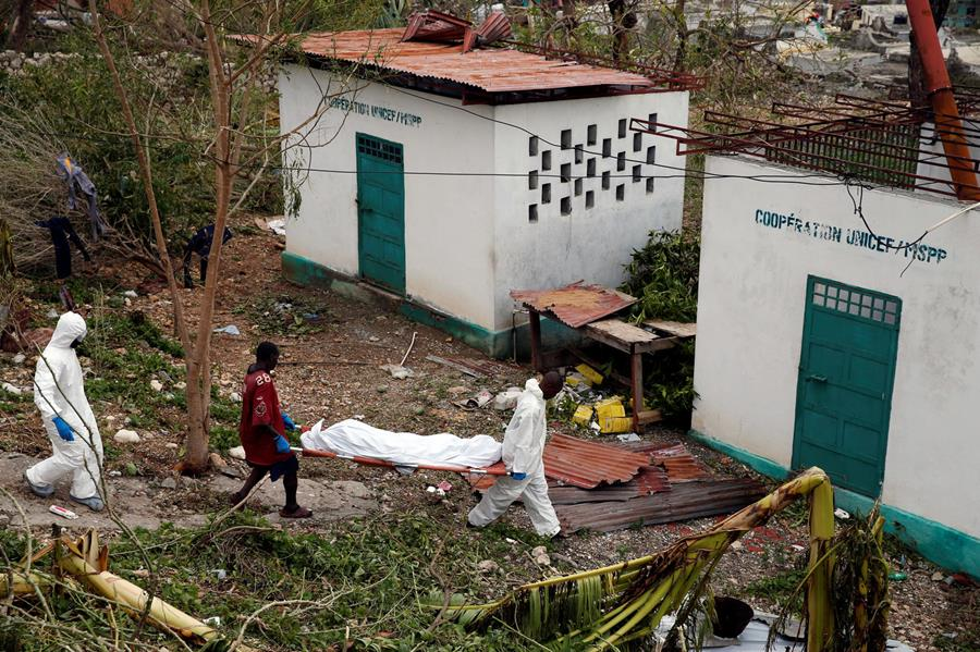 Workers carry a dead body after Hurricane Matthew passed Jeremie, Haiti.